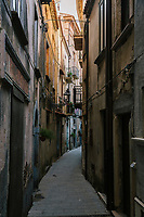 """PISCIOTTA, ITALY - 22 APRIL 2018: Narrow streets are seen here in the historical center of Pisciotta, Italy, on April 22nd 2018.<br /> <br /> Former restaurant owners Donatella Marino and her husband Vittorio Rimbaldo have spent the recent years preparing and selling salted anchovies, called alici di menaica, to a growing market thanks to a boost in visibility from the non-profit Slow Food.  The ancient Menaica technique is named after the nets they use brought by the Greeks wherever they settled in the Mediterranean. Their process epitomizes the concept of slow food, and involves a nightly excursion with the special, loose nets that are built to catch only the larger swimmers. The fresh, red anchovies are immediately cleaned and brined seaside, then placed in terracotta pots in between layers of salt, to rest for three months before they're aged to perfection.While modern law requires them to use PVC containers for preserving, the government recently granted them permission to use up to 10 chestnut wood barrels for salting in the traditional manner. The barrels are """"washed"""" in the sea for 2-3 days before they're packed with anchovies and sea salt and set aside to cure for 90 days. The alici are then sold in round terracotta containers, evoking the traditional vessels that families once used to preserve their personal supply.<br /> <br /> Unlike conventional nets with holes of about one centimeter, the menaica, with holes of about one and half centimeters, lets smaller anchovies easily swim through. The point may be to concentrate on bigger specimens, but the net also prevents overfishing."""