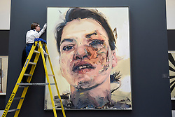 "© Licensed to London News Pictures. 21/06/2019. LONDON, UK. A technician inspects ""Shadow Head"", 2007-2013, by Jenny Saville (Est. GBP 3-5m) at the preview of a Contemporary Art auction at Sotheby's New Bond Street.  The sales take place 26 and 27 June 2019.  Photo credit: Stephen Chung/LNP"