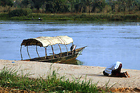 Niger, Boubon, 2007. A Muslim pirogue driver takes a moment for evening prayer by the banks of the Niger River.