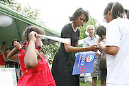 Michelle Obama, wife of Democratic presidential hopeful Senator Barack Obama, signs autographs for supporters as her daughter Sasha watches during a rally in Concord, New Hampshire June, 2, 2007. .