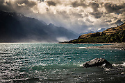 Sun rays break through and illuminate the Humboldt Mountain range over Lake Wakatipu, New Zealand.