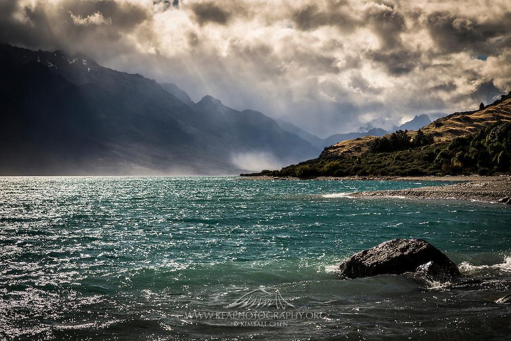 Sun rays break through and illuminate the Humboldt Mountain range over Lake Wakatipu, New Zealand.