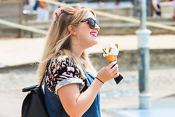 © Licensed to London News Pictures. 13/07/2019. Brighton, UK. A woman enjoys an ice cream in Brighton and Hove as was weather continues to hit the seaside resort. Photo credit: Hugo Michiels/LNP