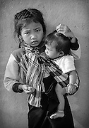 A Khamu girl caring for a child in her mountain village near Luang Prabang, Laos.