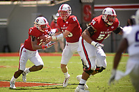 Wolfpack quarterback Ryan Finley hands off to running back Nyheim Hines (7).