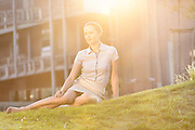Relaxed young businesswoman sitting on office lawn