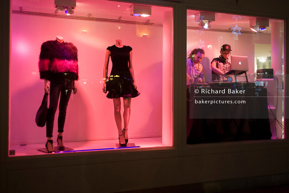 Two young DJs play loud music from inside a window of a fashion retailer in Carnaby Street, London.