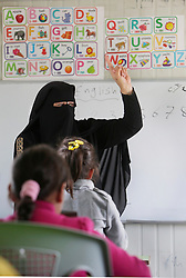 @ Licensed to London News Pictures 30/03/2015<br /> Azraq, Jordan -  A Jordanian teacher takes catch-up classes with Syrian refugee children in Azraq, a rural town in eastern Jordan, close to the Azraq UNHCR refugee camp. Local Jordanian charities set up the classes in portacabins, as the majority of Syrian children living outside the camp were unable to attend local schools due to lack of spaces.<br /> Photo: Anna Branthwaite/LNP