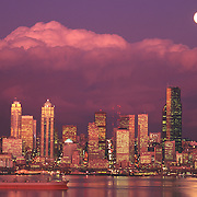 Seattle Washington USA city skyline reflected in Elliot Bay at sunset with full moon rising above cloud bank<br />