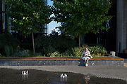 An elderly lady sits reading by fountains in evening sunshine in Nine Elms, on 7th July 2018, in London, England.