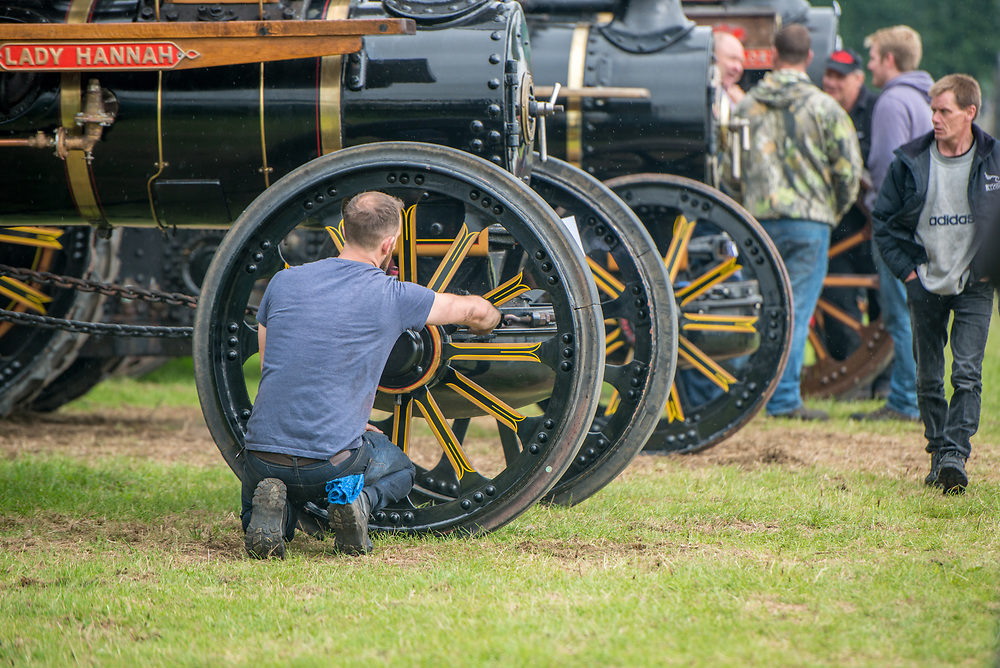 Facing his back to the camera a man uses rag to clean up wheel of steam engine tractor,  Masham, North Yorkshire, UK