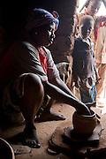 Woman making a clay pot inside a mud hut in Sindou, Burkina Faso