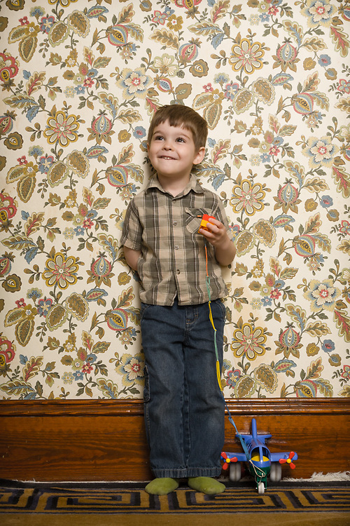 Photo of boy with his toy in front of crazy wallpaper at his house.