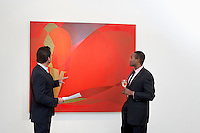 Two males talking over painting in museum