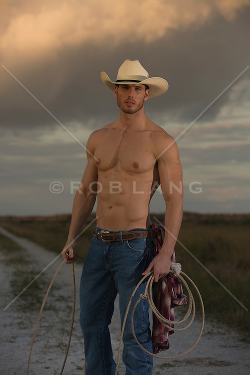 shirtless All American cowboy on a dirt road with a lasso