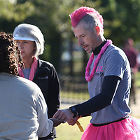 Adam Morris passes out door prize tickets to Survivors Saturday at the Hope Continues 5k that he put together for Breast Cancer