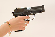 side view of a woman holding and aiming a Czech CZ-99 9mm parabelum semi-automatic hand gun finger on trigger, Cut out on white background