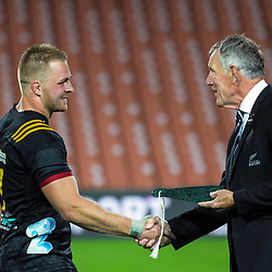 Sam Cane is presented with a mere for his 100th Super Rugby match by NZ Rugby's Maurice Trapp after the Super Rugby match between the Chiefs and Highlanders at FMG Stadium in Hamilton, New Zealand on Friday, 30 March 2018. Photo: Dave Lintott / lintottphoto.co.nz