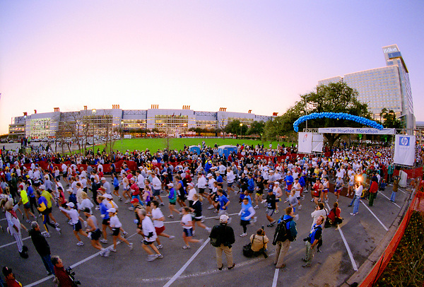 Stock photo of Houston marathon participants running by the George R. Brown Convention Center