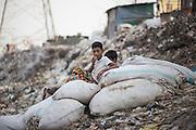 Boys take a break in the trash in Kamrangirchar, Dhaka.