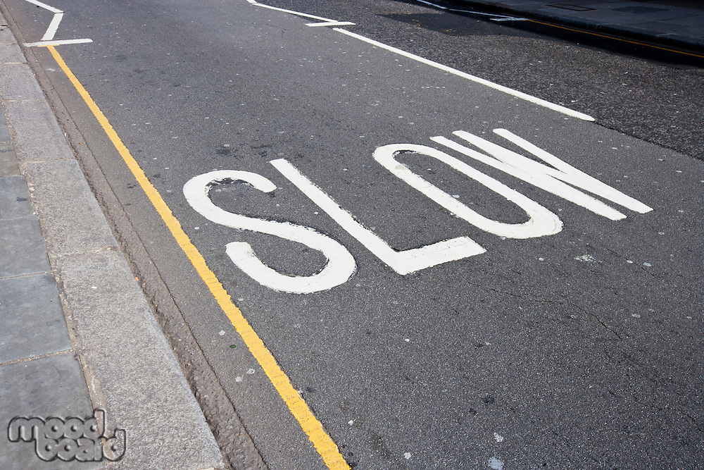 Close-Up of road marking saying Slow in London, UK