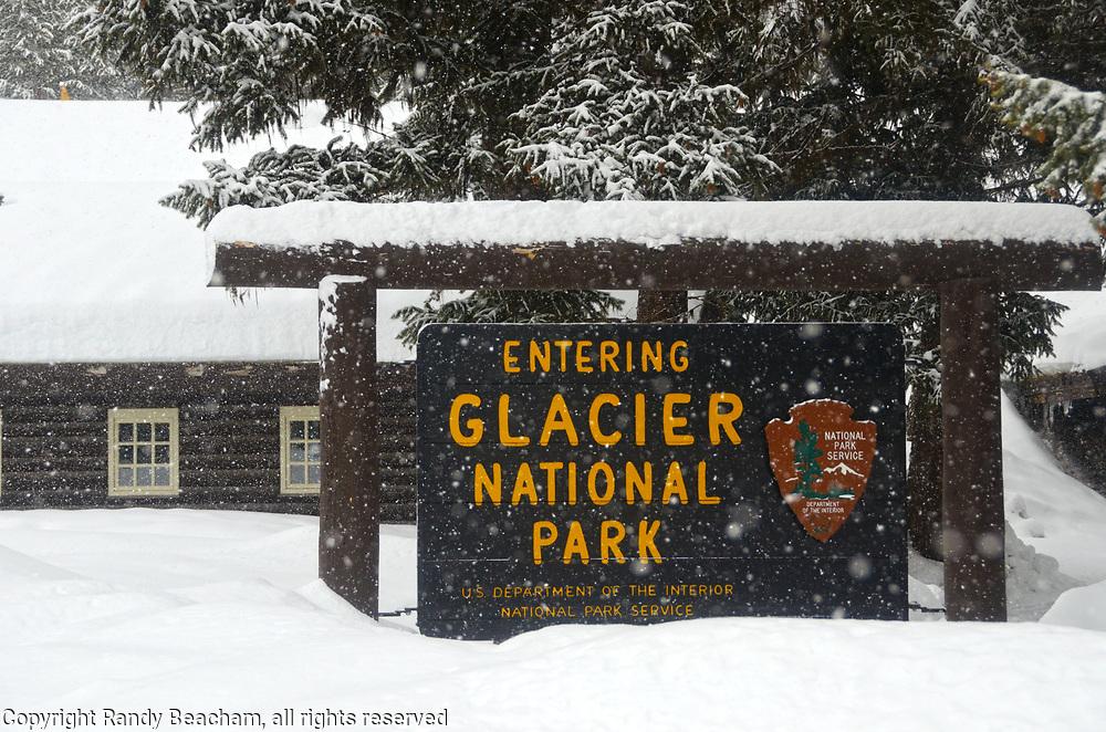 Glacier National Park entrance sign in winter 2017 at Polebridge Ranger Station. Glacier National Park, northwest Montana.