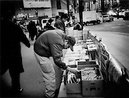 Discarded and discounted magazines, quickly collected from commuter trains, are sold by homeless man for food money on a Shinjuku street corner, Tokyo, Japan.