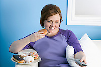 Overweight woman watching television, eating
