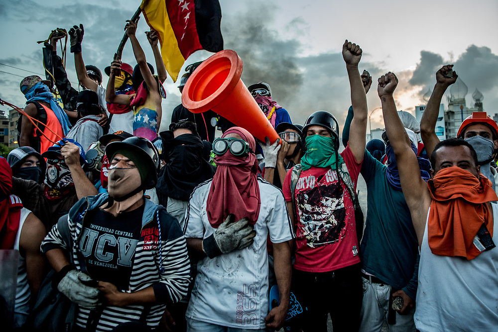 CARACAS, VENEZUELA - MAY 26, 2017:  Anti-government protesters celebrate and sing the national anthem in unison after taking back control of the main highway that runs through Caracas from government security forces. The streets of Caracas and other cities across Venezuela have been filled with tens of thousands of demonstrators for nearly 100 days of massive protests, held since April 1st. Protesters are enraged at the government for becoming an increasingly repressive, authoritarian regime that has delayed elections, used armed government loyalist to threaten dissidents, called for the Constitution to be re-written to favor them, jailed and tortured protesters and members of the political opposition, and whose corruption and failed economic policy has caused the current economic crisis that has led to widespread food and medicine shortages across the country.  Independent local media report nearly 100 people have been killed during protests and protest-related riots and looting.  The government currently only officially reports 75 deaths.  Over 2,000 people have been injured, and over 3,000 protesters have been detained by authorities.  PHOTO: Meridith Kohut