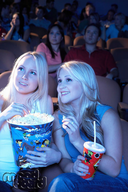 Smiling Friends sitting in theatre with popcorn and soda Watching Movie