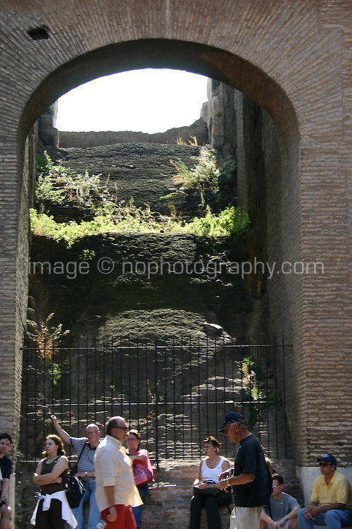 tourists at arch in the ancient roman monument, the Colosseum, Rome, Italy.<br />