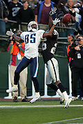 OAKLAND, CA - DECEMBER 19:  Wide receiver Derrick Mason #85 (caught 9 passes for 121 yards and a touchdown) of the Tennessee Titans stretches for a pass just out of reach while defended by cornerback Denard Walker #25 of the Oakland Raiders at Network Associates Coliseum on December 19, 2004 in Oakland, California. The Raiders defeated the Titans 40-35. ©Paul Anthony Spinelli *** Local Caption *** Derrick Mason;Denard Walker