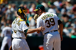 OAKLAND, CA - AUGUST 04:  Dustin Garneau #3 of the Oakland Athletics talks to Blake Treinen #39 during a mound visit during the eighth inning against the St. Louis Cardinals at the RingCentral Coliseum on August 4, 2019 in Oakland, California. The Oakland Athletics defeated the St. Louis Cardinals 4-2. (Photo by Jason O. Watson/Getty Images) *** Local Caption *** Dustin Garneau; Blake Treinen