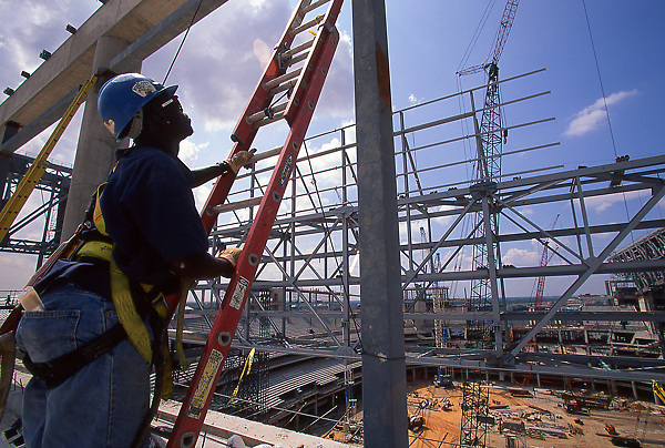Stock photo of a man climbing a ladder at the construction site of Reliant Stadium in Houston Texas