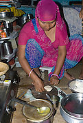 India, Rajasthan, Jaipur woman preparing food in her home