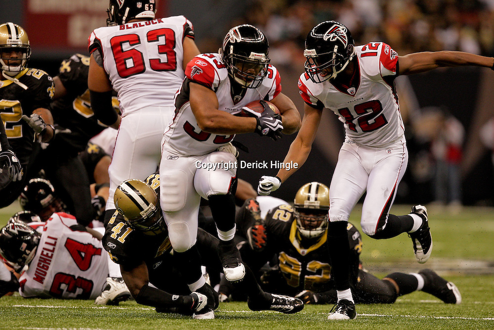 2009 November 02: Atlanta Falcons running back Michael Turner (33) breaks away from the tackle of New Orleans Saints safety Roman Harper (41) during a 35-27 win by the Saints over the Falcons at the Louisiana Superdome in New Orleans, Louisiana.