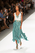 Dress with a flowing Fortuny-pleated sirt with a kelp-shaped hem and white V-neck top wih turquoise belt and bodice details. By Carlos Miele at the Spring 2013 Mercedes-Benz Fashion Week in New York.