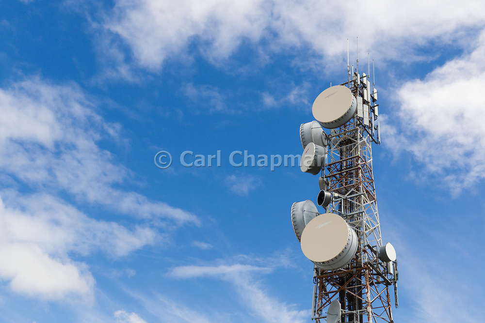Urban provincial  cellular, microwave and telecom communications systems lattice tower under cloudy sky in Rockhampton, Queensland, Australia.