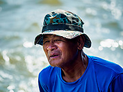 29 OCTOBER 2018 - PHRA PRADAENG, SAMUT PRAKAN, THAILAND: A man watches the long boat races in Phra Pradaeng. The longboat races go about one kilometer down the Chao Phraya River to the main pier in Phra Pradaeng. The boats are crewed by about 20 oarsmen. Longboat racing traditionally marks the end of the Buddhist Rains Retreat (called Buddhist Lent) in Thai riverside communities.       PHOTO BY JACK KURTZ