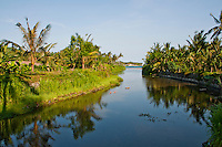 River flowing through palms to the ocean at Candidasa, Bali, Indonesia