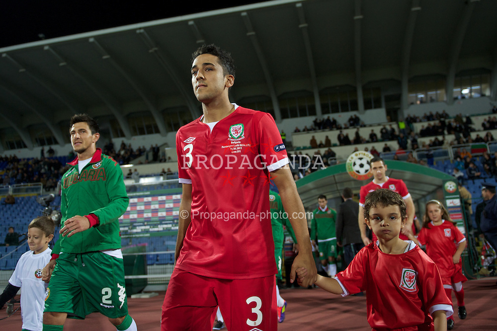 SOFIA, BULGARIA - Tuesday, October 11, 2011: Wales' Neil Taylor walks out with a mascot before the UEFA Euro 2012 Qualifying Group G match against Bulgaria at the Vasil Levski National Stadium. (Pic by David Rawcliffe/Propaganda)