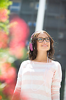 Smiling young woman looking away while listening music on sunny day