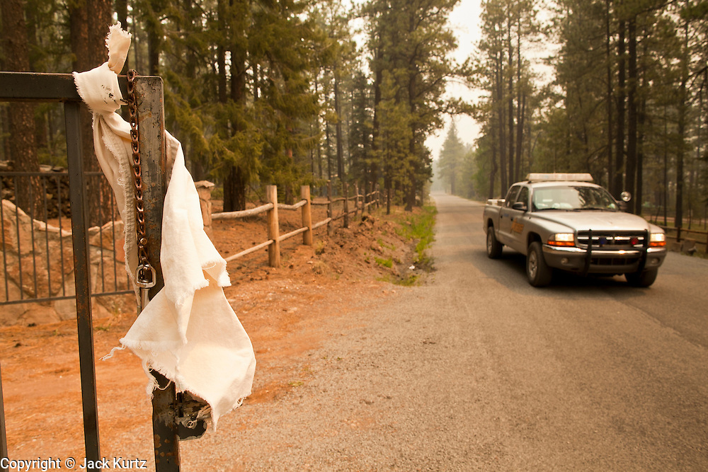 "05 JUNE 2011 - GREER, AZ:  A sheriff's vehicle passes an empty residence in Greer Sunday. Officials have asked residents to tie white towels to their doors and gates so officials know the residence is empty. The fire grew to more than 180,000 acres by Sunday with zero containment. A ""Type I"" incident command team has taken command of the fire.    PHOTO BY JACK KURTZ"