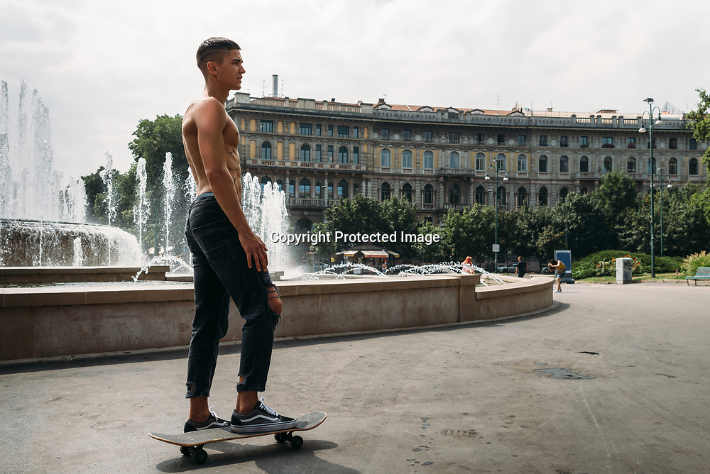 Young athletic man on a skateboard with traditional Italian buildings in the background