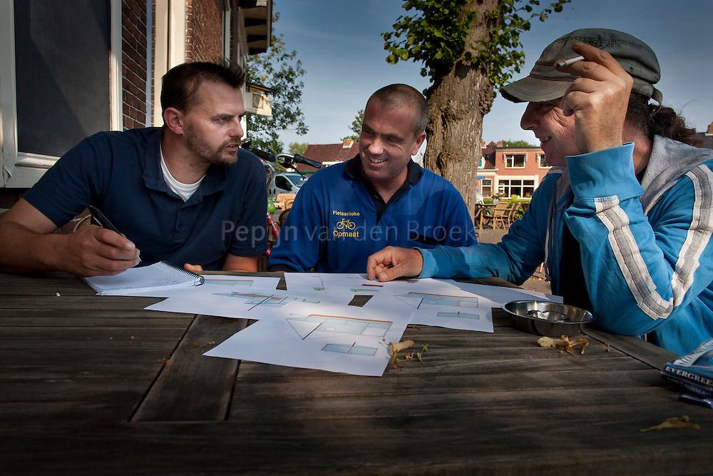 Nederland, Zuidwolde 20110728. Steven Boekschoten, Egbert kamstra en Henk Leber gebogen over het ontwerp voor een melkpakkenboot, waarmee ze naar Engeland willen varen. foto: Pepijn van den Broeke.