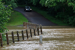 © Licensed to London News Pictures. 11/06/2012, Petworth, UK.  A car stops at the edge of a flooded road near Petworth, West Sussex, England as continuous rain cause flooding to many area, Monday, June 11, 2012. Photo credit : Sang Tan/LNP