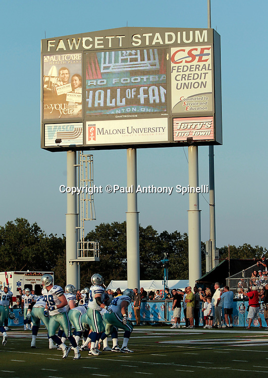 The Dallas Cowboys go through pregame warmups with the Fawcett Stadium scoreboard in the background prior to the NFL Pro Football Hall of Fame preseason football game between the Dallas Cowboys and the Cincinnati Bengals on Sunday, August 8, 2010 in Canton, Ohio. The Cowboys won the game 16-7. (©Paul Anthony Spinelli)