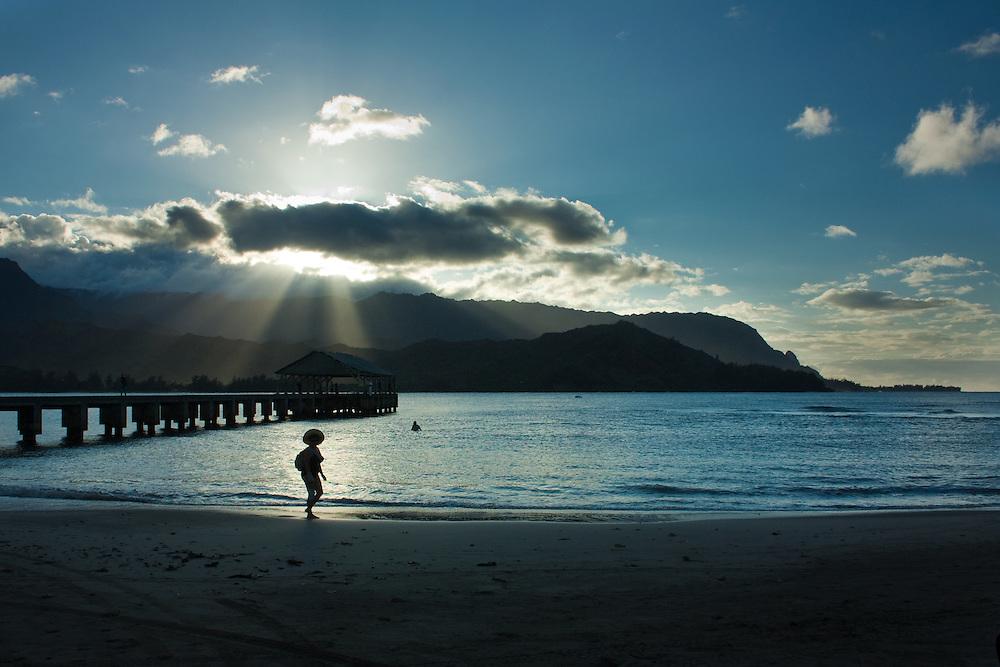 Woman on beach near Hanalei Bay Wharf at Sunset, Kauai, Hawaii