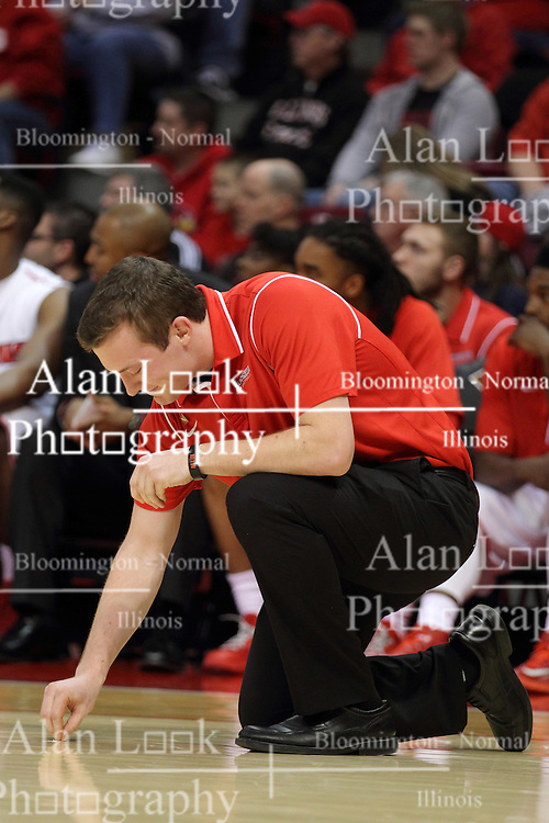 18 March 2015:  a person from the Illinois State bench crew attempts to pull up a wad of gum from the playing floor during an NIT men's basketball game between the Green Bay Phoenix and the Illinois State Redbirds at Redbird Arena in Normal Illinois