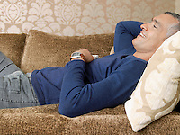 Smiling man laying on sofa